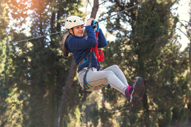 Girl enjoying activity in a climbing adventure park Happy school girl enjoying activity in a climbing adventure park on a sunny day zip line stock pictures, royalty-free photos & images