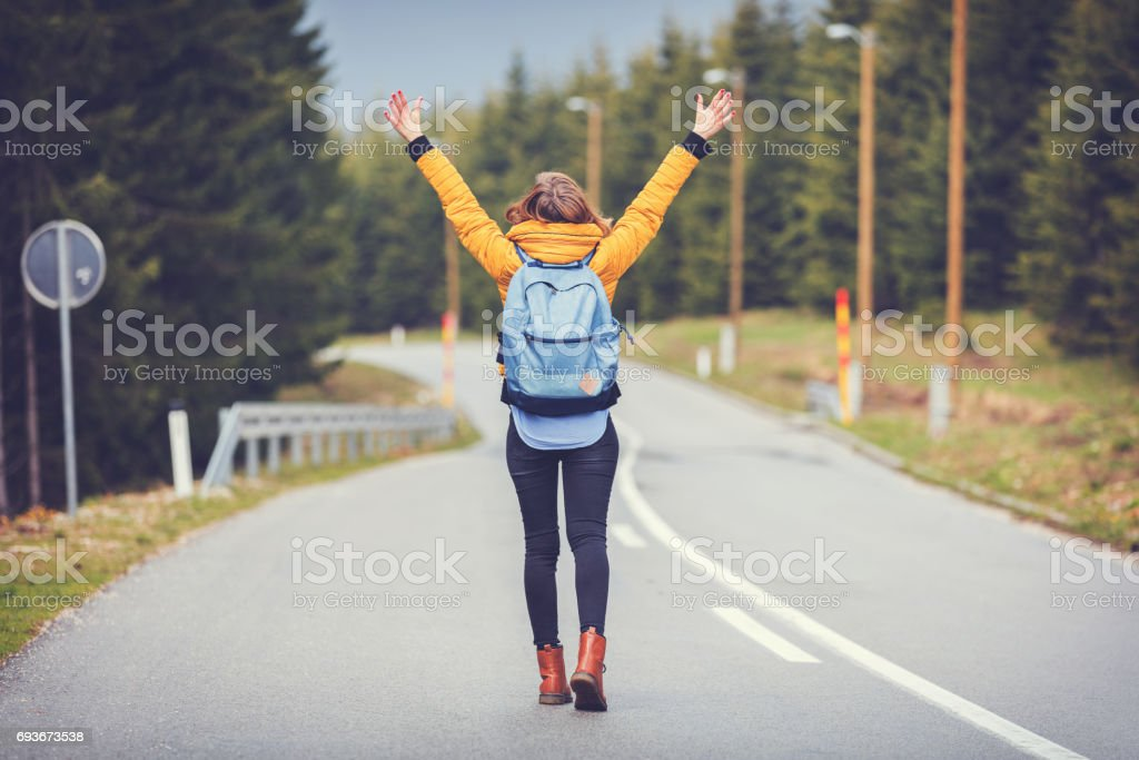 Girl enjoying alone on the road with arms wide open. stock photo