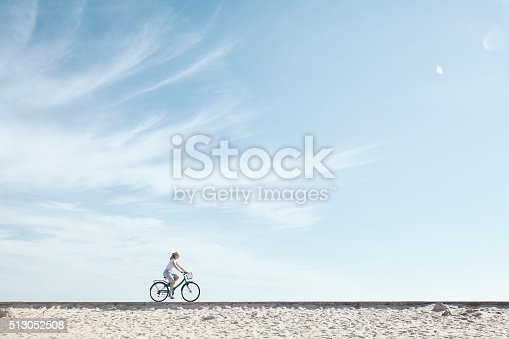 istock Girl enjoying bike ride under sky 513052508