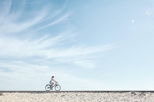Girl enjoying bike ride under sky stock photo