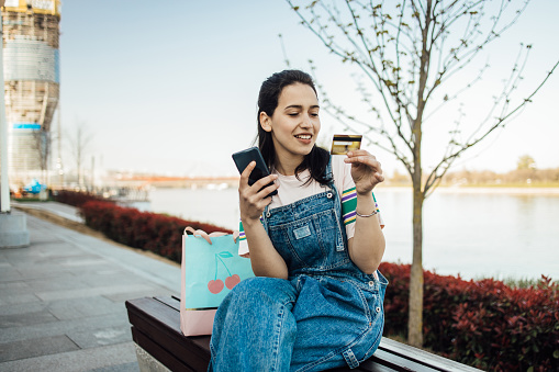 Girl enjoying by the river and using her credit card for online shopping