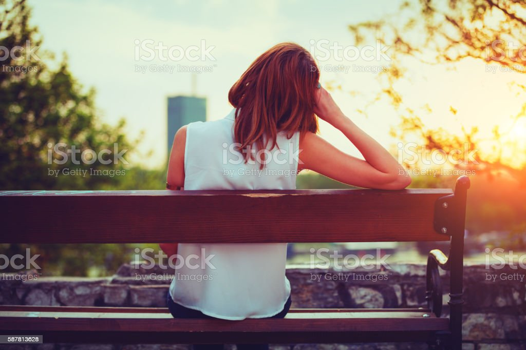 Girl enjoying city view from a bench. stock photo