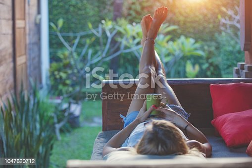 Girl enjoying early morning coffee on the garden sofa.