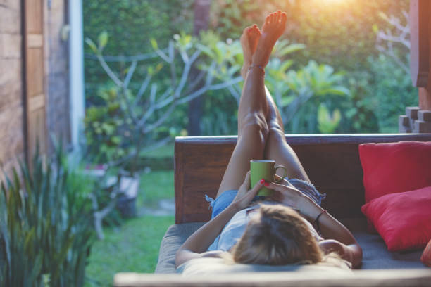 girl enjoying early morning coffee on the garden sofa. - resting stock pictures, royalty-free photos & images