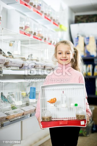 Little happy girl enjoying her purchase of canary bird in pet shop