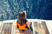 Little girl sitting on the back part of the ship while sailing on the Ionian sea in Greece. She put their feet in the blue sea and enjoy while waves massaging it. Girl is wearing a life jackets.