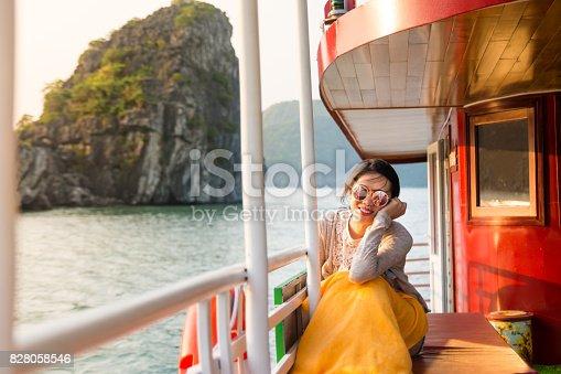 istock Girl enjoying last sunshine on a cruise boat 828058546