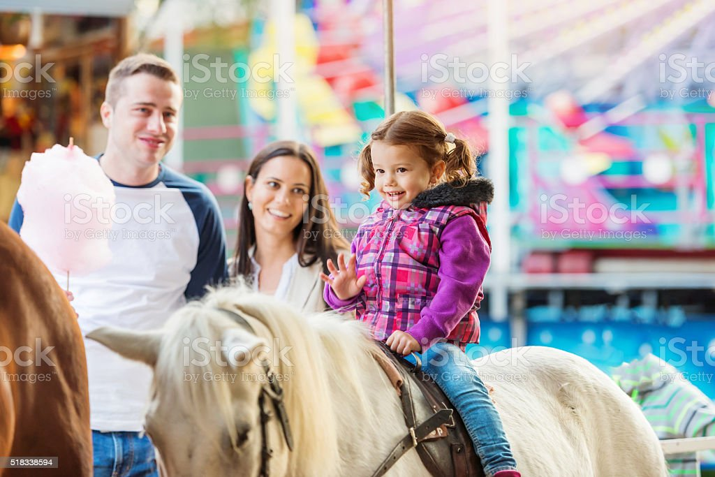 Girl enjoying pony ride, fun fair, parents watching her stock photo
