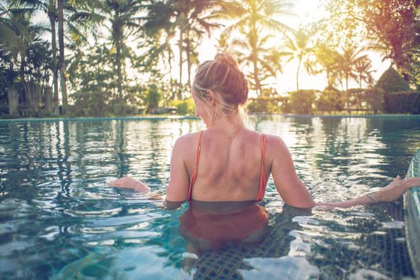Mädchen genießen Resort Spa Wellness im tropischen Paradies - Frau Swimmingpool im Luxus-Resort-Wellness-Refugium im Freien entspannen. Glückliches junges weibliche Modell entspannt auf Urlaubsreisen im Wasser ruht. – Foto