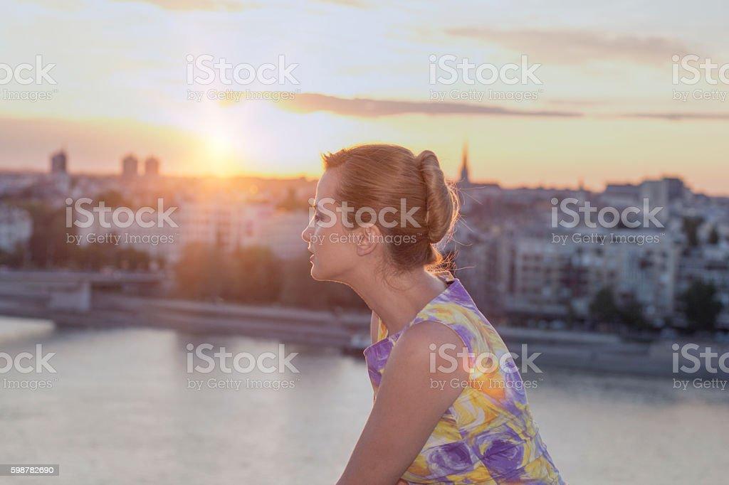 Girl enjoying scenic sunset in the city stock photo