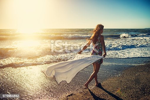 istock Girl enjoying sunset on a windy beach 979964842