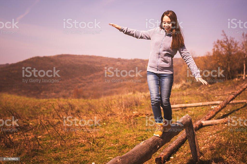 Girl enjoying the nature walking on the balance beam stock photo