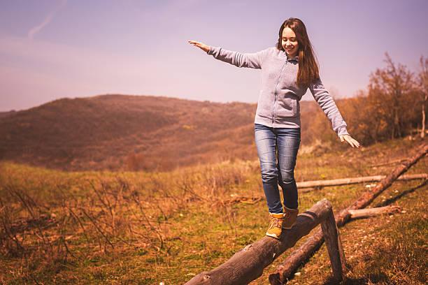 girl enjoying the nature walking on the balance beam - balance beam stock photos and pictures