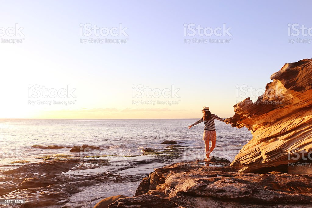 Girl enjoying the sunrise in front of the ocean stock photo