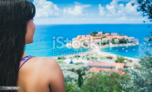 Girl enjoying beautiful view of a small island on her vacation. View of the Sveti Stefan island in Montenegro.