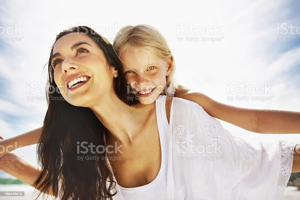 Girl enjoys a piggy back ride on mother royalty-free stock photo