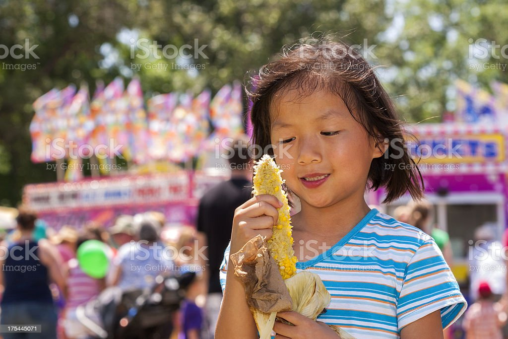 Girl enjoys corn on the cob at carnival stock photo