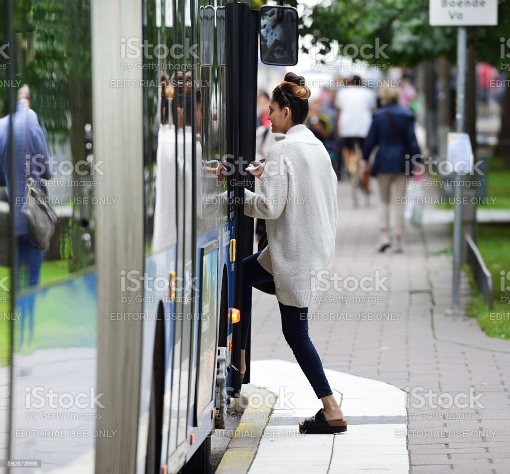 Girl enters bus, using phone as ticket stock photo