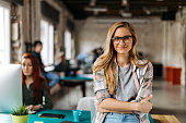 Portrait of a smiling young girl student in the start-up office. Standing with her glasses smiling at the camera while her colleagues are in the back of the classroom. Canon 5d mark 4 85mm lens