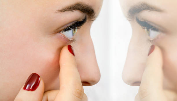 girl examines her eye in front of the mirror stock photo