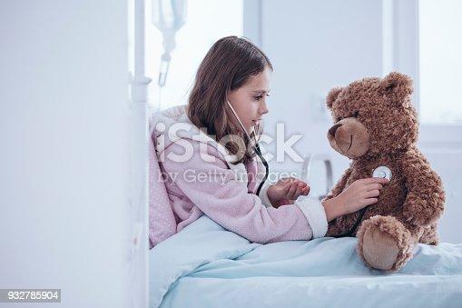 istock Girl examining teddy bear 932785904