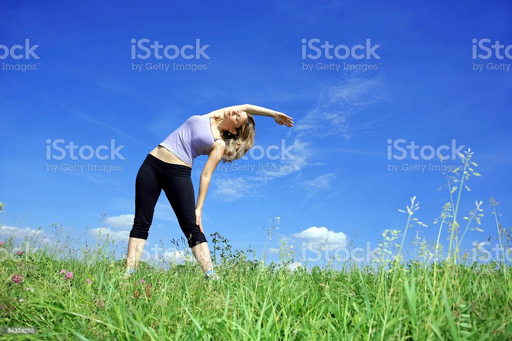 Girl exercising in meadow royalty-free stock photo