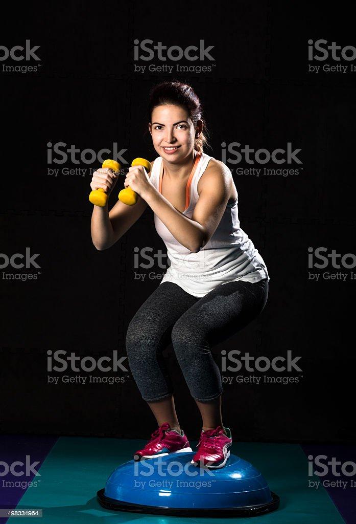 Girl exercising on bosu balance ball holding dumbbells in gym stock photo