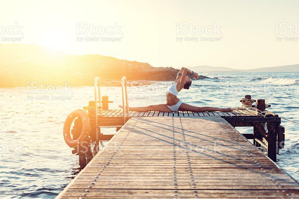 Girl exercising splits at the quay stock photo