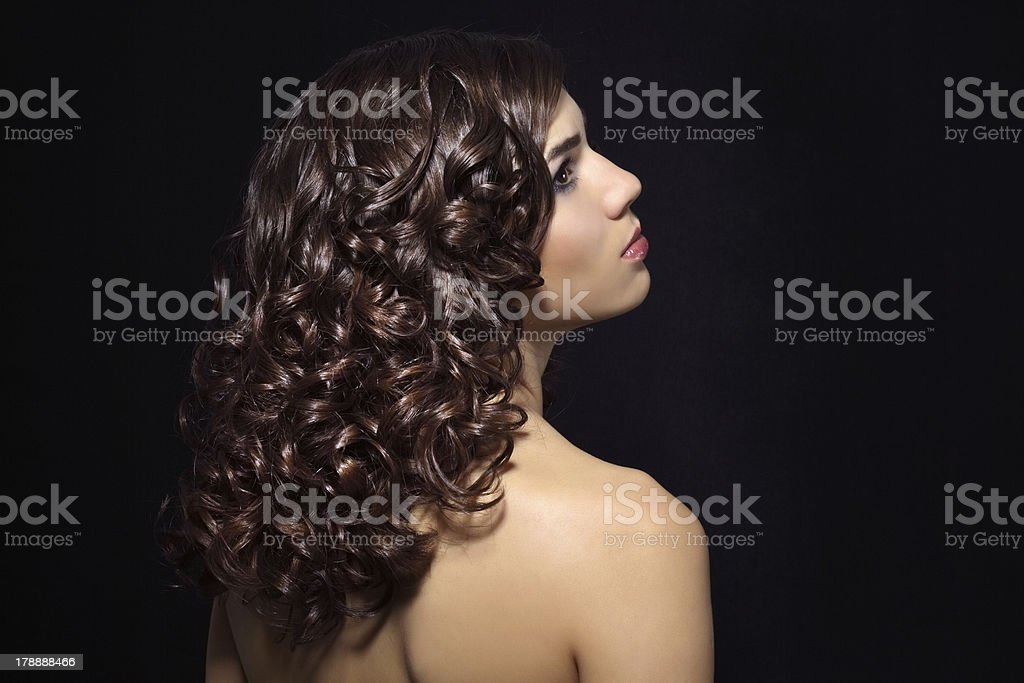 Girl faces away from camera showing off her curly brown hair royalty-free stock photo