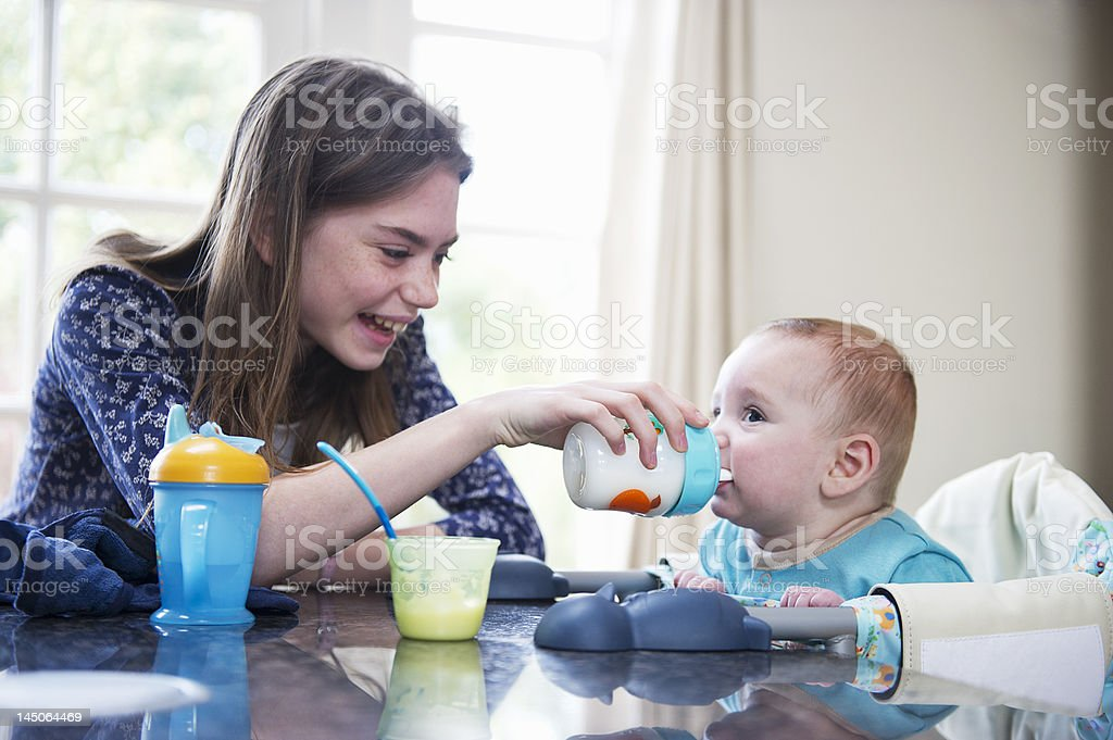 Girl feeding baby brother en la mesa - foto de stock