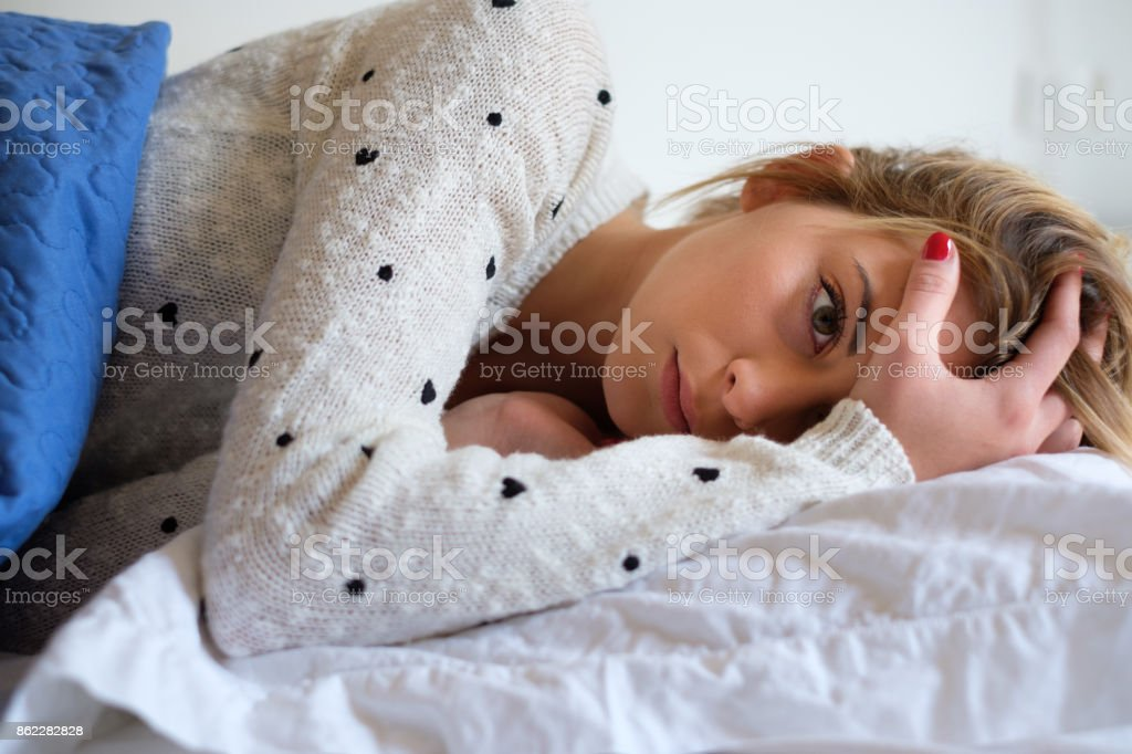 Girl feeling bad and trying to sleep stock photo