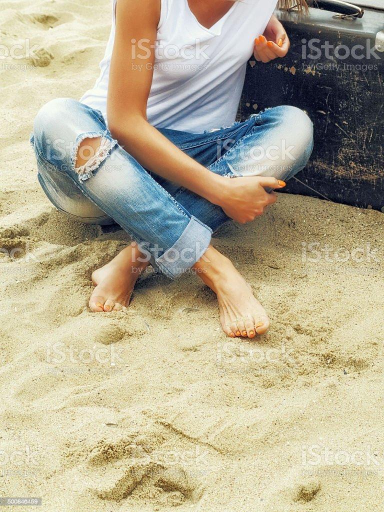girl  feet on sand near  sea with suitcase stock photo