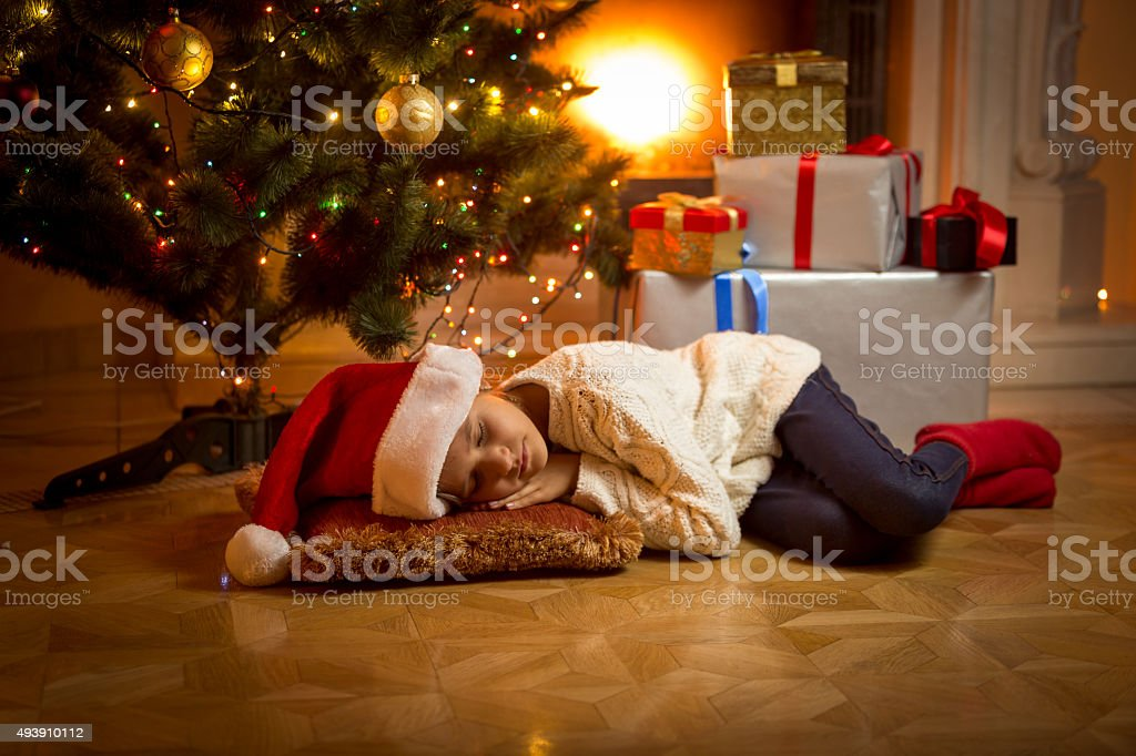 girl fell asleep under Christmas tree while waiting for Santa stock photo