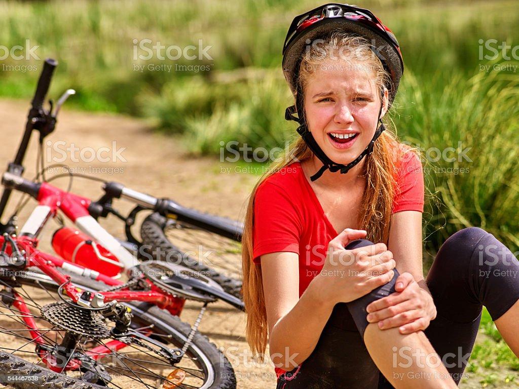Girl fell off bike. Cyclist keeps self for bruised knee. stock photo