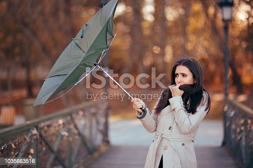 Autumn woman having problems in windy storm