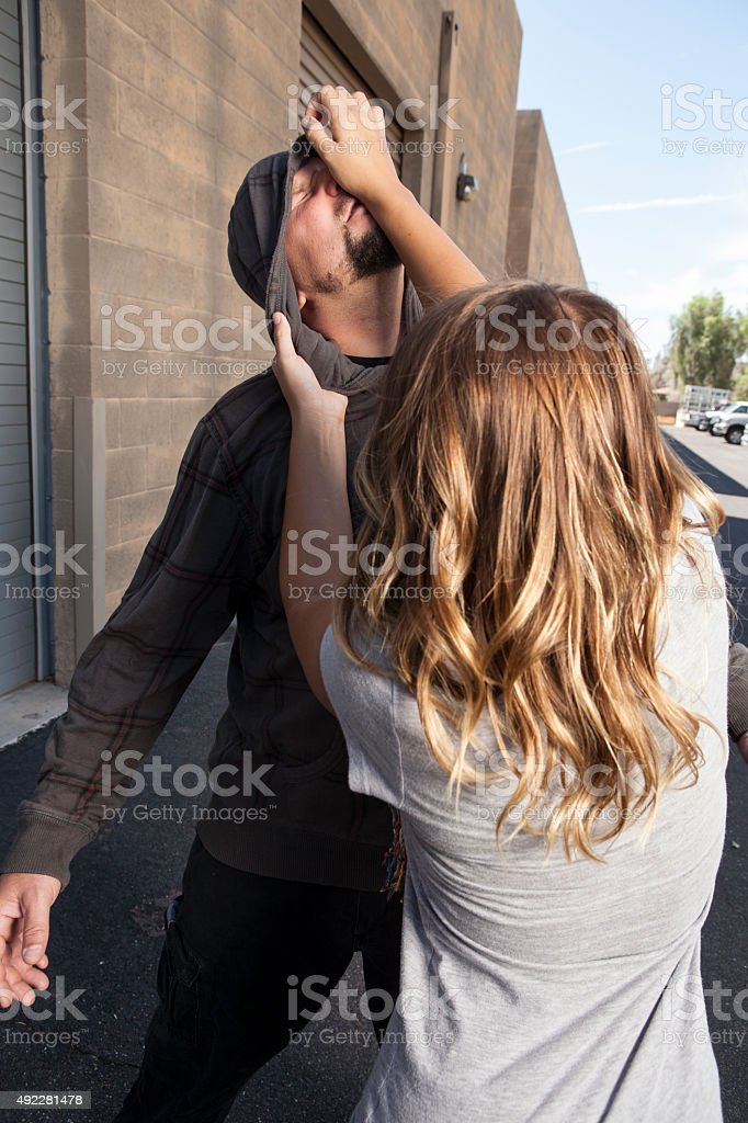 Girl fights off attacker in alley. stock photo