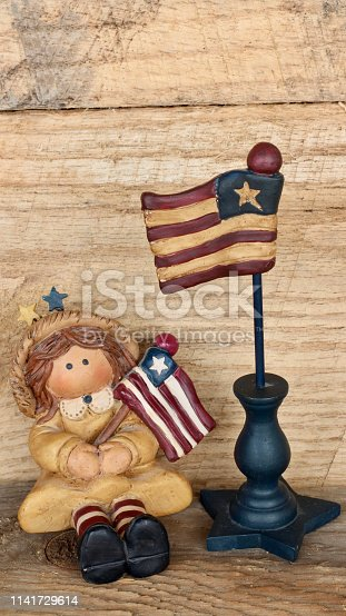 istock girl figurine holding american flag on wood background 1141729614