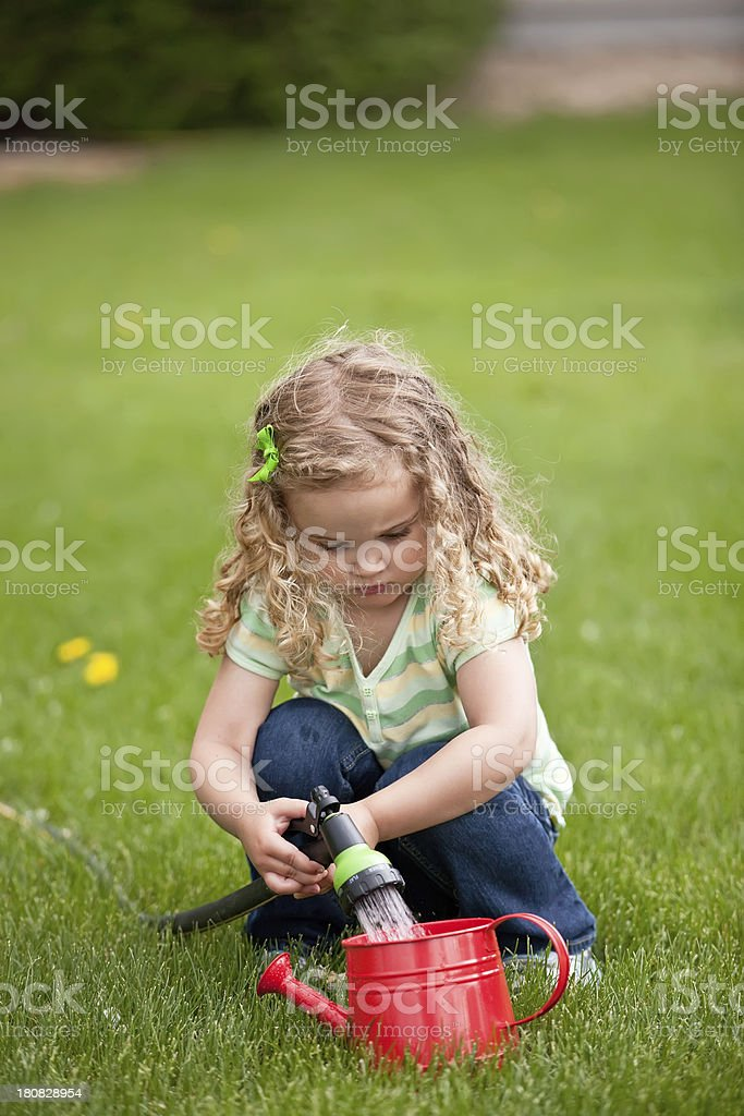 Young girl filling a red watering can with the garden hose.