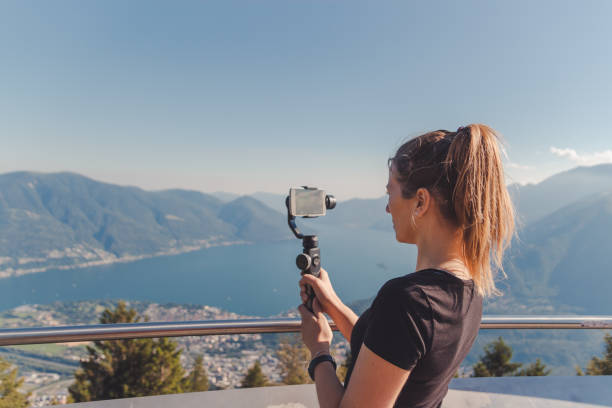 Girl filming with gimbal in the mountains over lake maggiore picture id1026201476?b=1&k=6&m=1026201476&s=612x612&w=0&h=olbyyr7lormhx532rnkcbmutnozzne3pz lqjfbnubq=