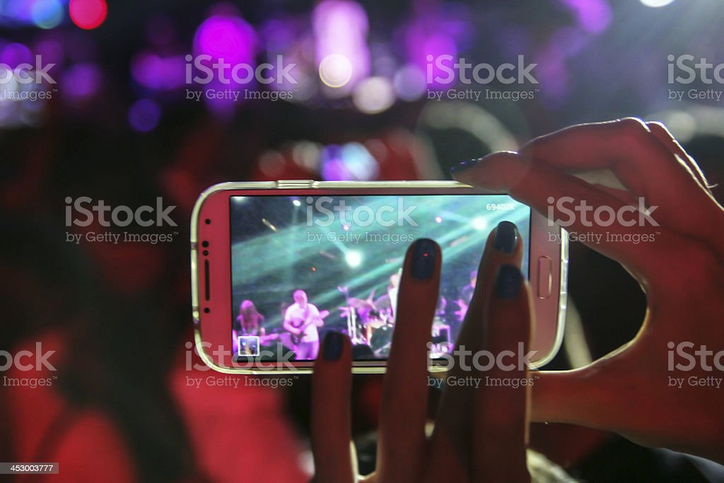 Girl filming with smartphone on concert in the nightclub stock photo