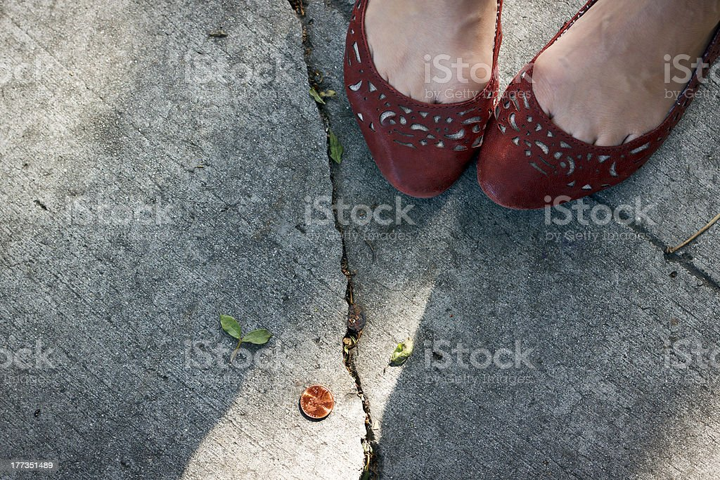 Girl finds a penny on the sidewalk. stock photo