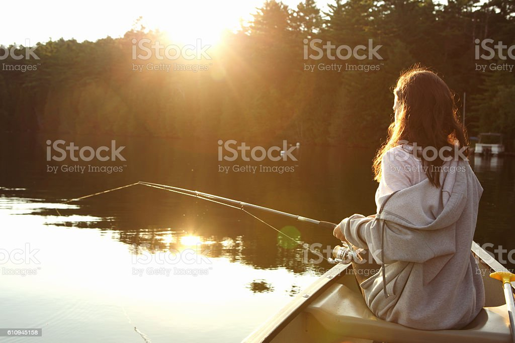 Girl fishing from a canoe at sunrise stock photo