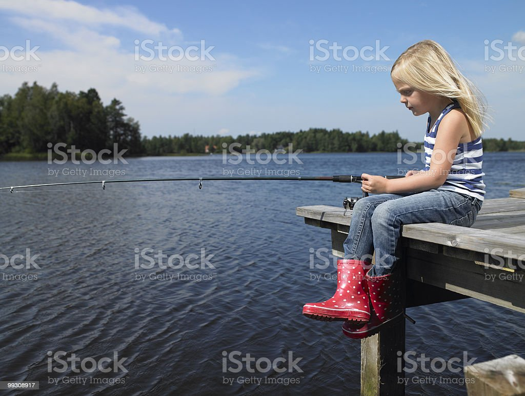 Girl fishing from a dock royalty-free stock photo