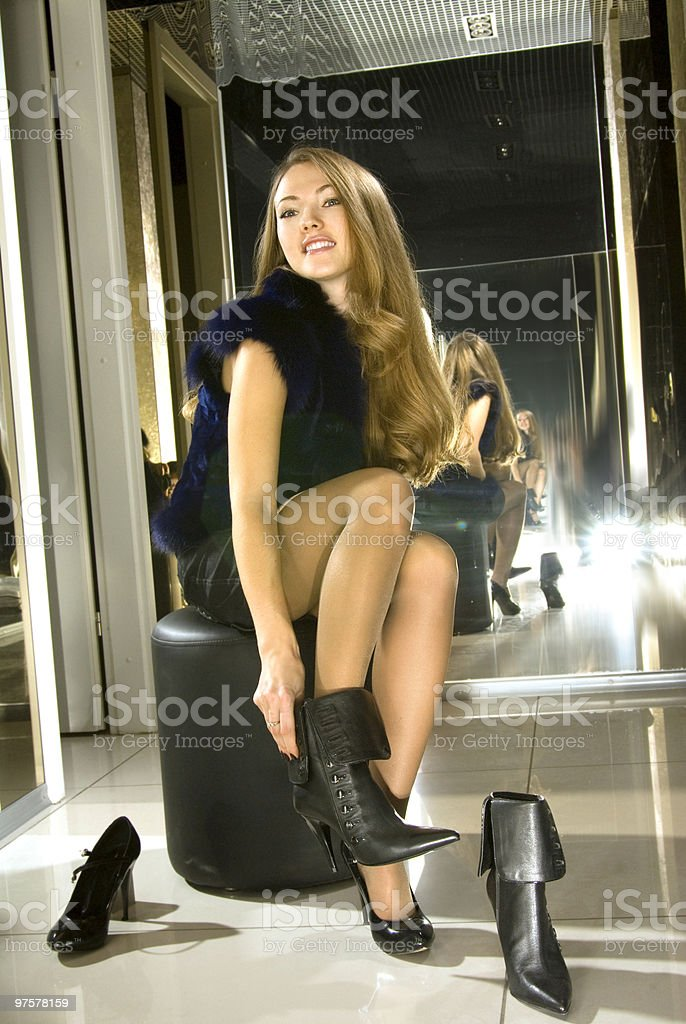 girl fits on boots in boutique royalty-free stock photo