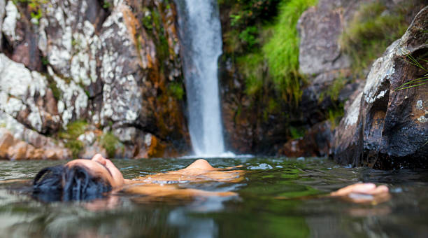 Girl floating at waterfall Girl floating at waterfall. goias stock pictures, royalty-free photos & images