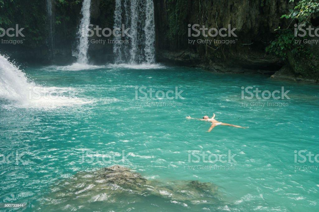 Girl floating in pool starfish pose stock photo