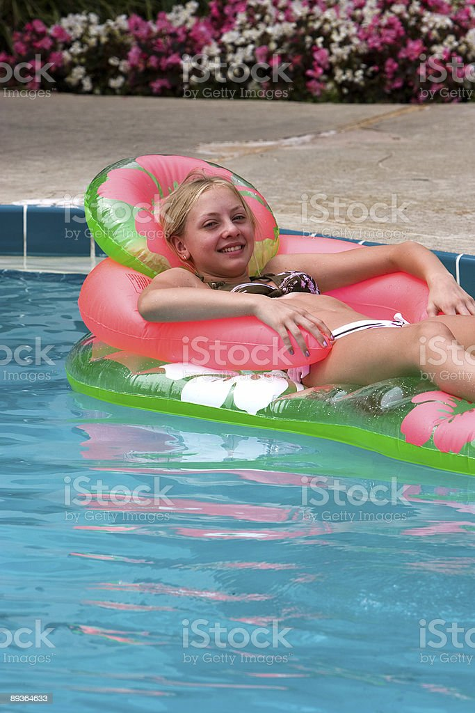 Girl floating in the pool royalty-free stock photo
