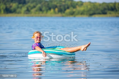 Side view of a young girl laying on her back in an inner tube float toy, floating on the water at the lake on a summer day. The girl is wearing a rash guard swim shirt and swim goggles, and she is smiling at the camera.