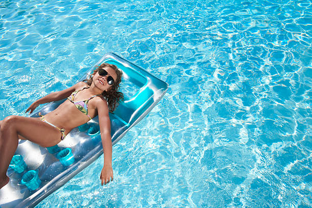 girl floating on raft in swimming pool - girl alone in swimsuit stock photos and pictures