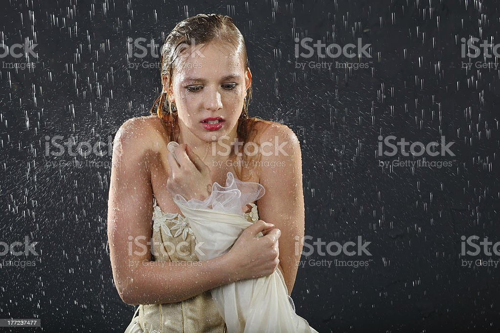 Girl freezes in rain and tries to keep warm stock photo